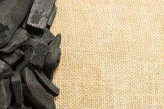 Schwarze Holzkohle auf Juteleinwandsack-Beschaffenheitshintergrund Lizenzfreie Stockbilder