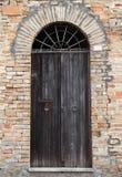 Schwarze Holztür mit Bogen in der alten Steinwand Lizenzfreie Stockbilder