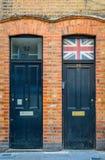 Schwarze Holztür mit der Staatsflagge des Vereinigten Königreichs über der Tür lizenzfreie stockfotografie