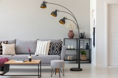 Schwarze industrielle Lampe nahe bei grauer Couch mit kopierten Kissen, Couchtisch und Puff im einfarbigen Wohnzimmer lizenzfreies stockbild