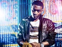 Schwarze Jugend mit Jacke und bunten Lichtern Stockfoto