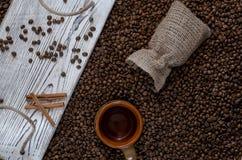 Schwarze Kaffeebohne auf dem Tisch zerstreut von einer einfachen Tasche lizenzfreie stockbilder
