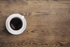 Schwarze Kaffeetasse auf alter Draufsicht des Holztischs Stockfoto
