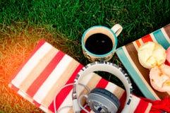 Schwarze Kaffeetassen legen auf das Gras mit Bonbons Süßigkeit, mit einem mus Stockfoto