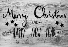 Schwarze Kalligraphie-frohe Weihnachten und guten Rutsch ins Neue Jahr, hölzerner Hintergrund Stockbilder
