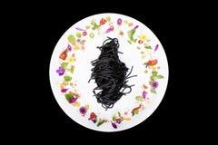 Schwarze Kalmarspaghettis in der Platte mit Blumendekoration auf schwarzem Hintergrund stockfotografie