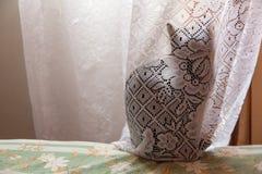 Schwarze Katze versteckt hinter einem Vorhang des lichtdurchlässigen Weiß lizenzfreies stockfoto