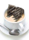 Schwarze Kekse eingetaucht in Kaffee mit Milch Lizenzfreie Stockfotos