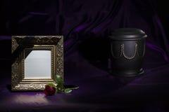 Schwarze Kirchhofurne mit goldenem Trauerrahmen des Rotrosen-freien Raumes auf tiefpurpurnem Hintergrund lizenzfreie stockfotografie