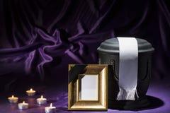 Schwarze Kirchhofurne mit goldenem Trauerrahmen, Kerzen und weißem Band auf tiefpurpurnem Hintergrund Lizenzfreies Stockbild