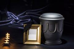 Schwarze Kirchhofurne mit goldenem Trauerrahmen und Los Kerzen auf tiefem blauem Hintergrund Lizenzfreie Stockfotos