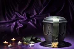 Schwarze Kirchhofurne mit Kerzen und tiefgrünes Band auf dunklem purpurrotem Hintergrund Lizenzfreies Stockfoto
