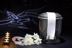 Schwarze Kirchhofurne mit Kerzen und weißer Chrysantheme und weißes Band Stockfotografie