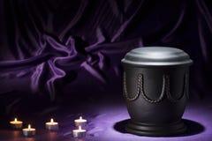 Schwarze Kirchhofurne mit Los Kerzen auf tiefpurpurnem Hintergrund Stockbild