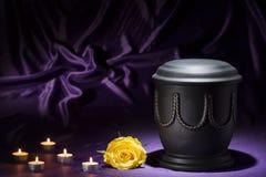 Schwarze Kirchhofurne mit Los von Kerzen und von Gelbrose auf tiefpurpurnem Hintergrund Stockfotografie