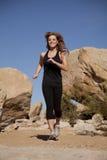 Schwarze Kleidung der Frau, die Lächeln laufen lässt Lizenzfreie Stockfotos