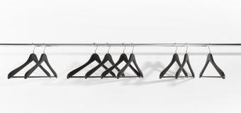 Schwarze Kleidungaufhängungen auf weißem Hintergrund Stockbild