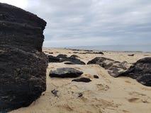Schwarze Kohle auf dem weißen Sandstrand der Düne von Pilat, im Arcachon-Buchtbereich, nahe gelegenes Bordeaux, Frankreich stockfotografie