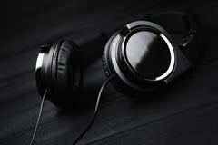 Schwarze Kopfhörer auf schwarzem hölzernem dunklem Hintergrund Lizenzfreies Stockbild