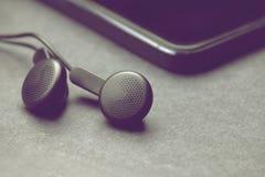 Schwarze Kopfhörer mit Smartphonehintergrund Lizenzfreies Stockfoto