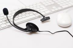 Schwarze Kopfhörer des Büros auf weißer Tastatur Lizenzfreie Stockfotos