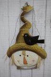 Schwarze Krähe trotzt dem Rand des lächelnden Vogelscheuchen-Hutes Lizenzfreies Stockfoto