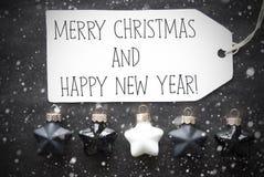 Schwarze Kugeln, Schneeflocken, simsen frohe Weihnachten und guten Rutsch ins Neue Jahr Lizenzfreie Stockfotos
