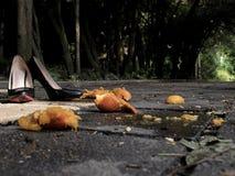Schwarze lackierte Frauenschuhe mit Fersen in der Straße nahe der zerquetschten Mandarine lizenzfreies stockfoto