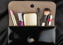 Schwarze Lackledertasche mit Kosmetik Lizenzfreie Stockfotos