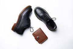 Schwarze lederne Derby-Schuhe mit Polyurethansohlen und ein brauner Geldbeutel mit einem Knopf auf einem wei?en Hintergrund lizenzfreie stockbilder