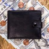 Schwarze lederne Geldbörse oben zu den Banknoten und zu den Münzen US geschlossen FI Stockfoto
