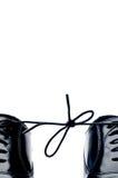 Schwarze lederne Schuhe mit ihren Spitzeen zusammen gebunden Lizenzfreie Stockfotos