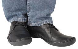 Schwarze Lederschuhe, graue Denimindigojeans, zufälliges men& x27; s-Turnschuhnahaufnahme, man& x27; s-Füße Detail, Fuß, Beine lo Lizenzfreie Stockfotos