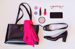 Schwarze Ledertasche, schwarze Schuhe, Smartphone, Gläser und Kosmetik Stockbild