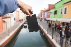 Schwarze leere Karte in den Händen eines jungen Mannes auf dem Hintergrund von farbigen Häusern und Kanal von Burano-Insel, Vened lizenzfreie stockbilder