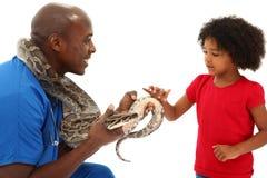Schwarze männliche Tierarzt-Holding-Schlange mit jungem Kind Lizenzfreie Stockfotos