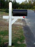 Schwarze Mailbox auf hölzernem Standplatz Stockfoto