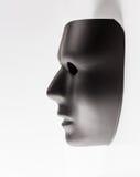 Schwarze Maske, die vom weißen Hintergrund auftaucht Lizenzfreies Stockfoto