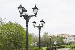 Schwarze Metalllaterne mit zwei touristisch unterzeichnen herein einen grünen Park Schwarze Laterne in einem grünen Park im Hinte stockfotografie