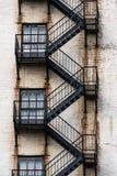 Schwarze Metallnotausgang-Treppe Zig Zag und Connect Windows auf dem Weg unten lizenzfreies stockfoto