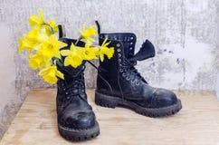 Schwarze militärische schlammige Schuhe mit gelben Narzissen Lizenzfreie Stockfotos