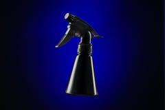 Schwarze Minisprühflasche über blauem Hintergrund Stockfoto