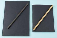 Schwarze Notizbücher und Bleistifte auf blauem Hintergrund Stockfotografie