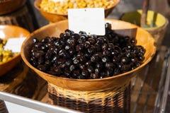 Schwarze Oliven im Korb für Verkauf am Landwirtmarkt lizenzfreies stockfoto