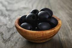 Schwarze Oliven von der Dose in der Schüssel auf Tabelle Lizenzfreie Stockbilder