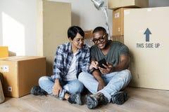 Schwarze Paare, die auf neues Haus sich bewegen Lizenzfreie Stockbilder