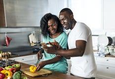 Schwarze Paare, die zusammen in der Küche kochen lizenzfreie stockfotos