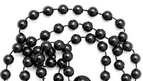 Schwarze Perlen auf einem weißen Hintergrund Lizenzfreie Stockfotografie