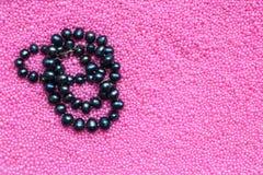 Schwarze Perlenperlen auf rosa Hintergrund, Kopienraum stockfoto