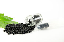 Schwarze Pillen gelegt auf einen weißen Hintergrund und in eine Glasflasche Stockfotos